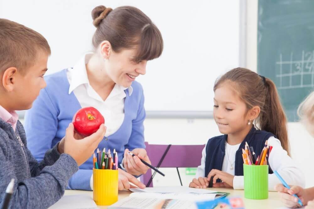 一つの机で先生と子どもが学習している様子