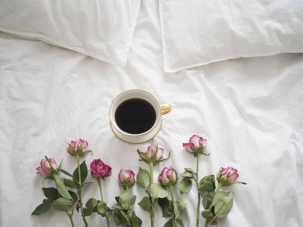 ベッドにコーヒーとバラ